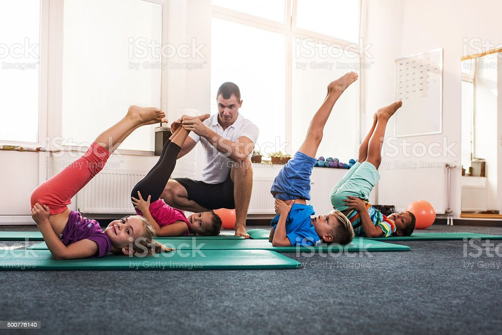 Group of children exercising with their legs up while having a...
