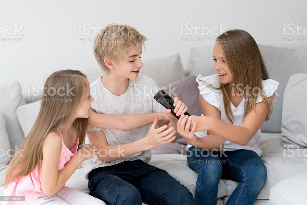 Kids fighting over the tv remote stock photo