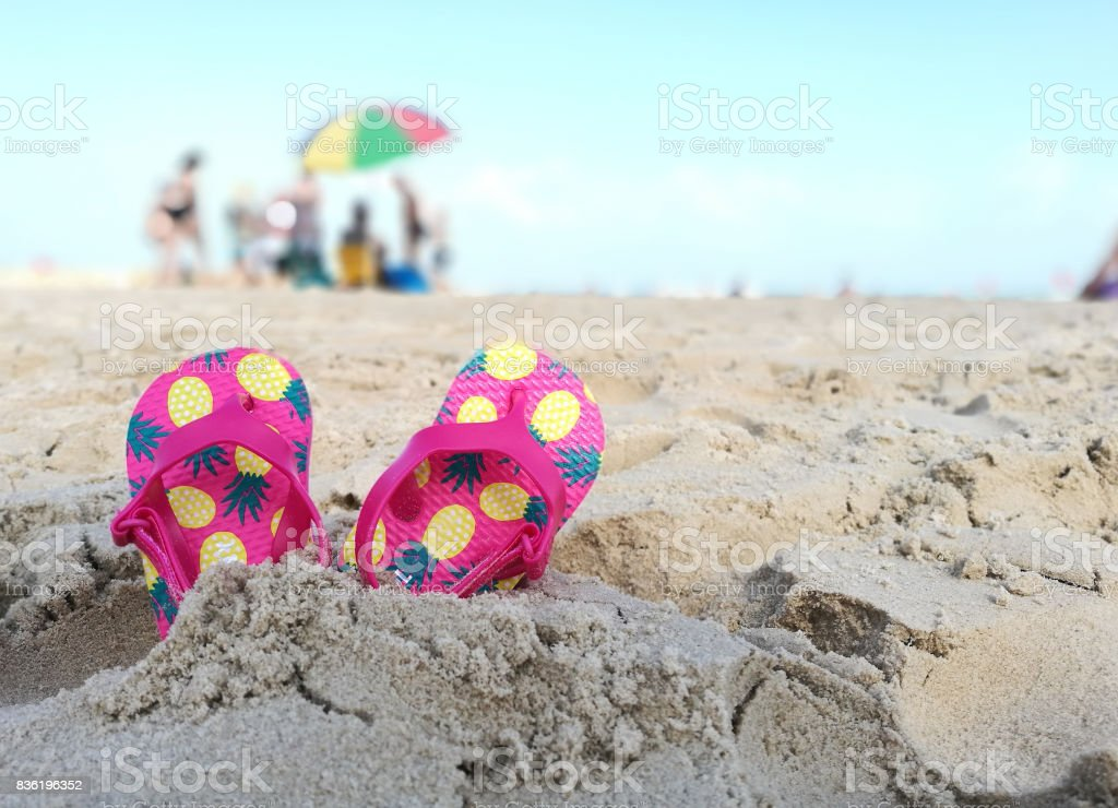 Kids flip flops on the beach stock photo
