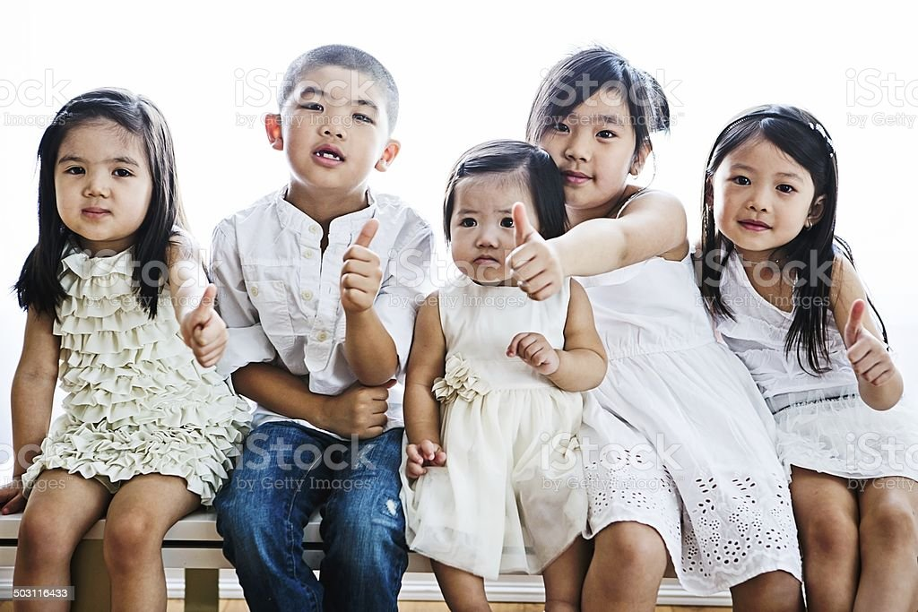 Kids giving thumbs up gesture. royalty-free stock photo
