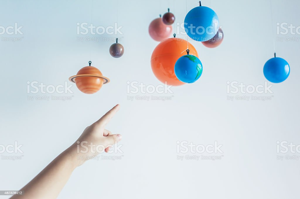 Kid's Hand Pointing at a Toy Solar System stock photo