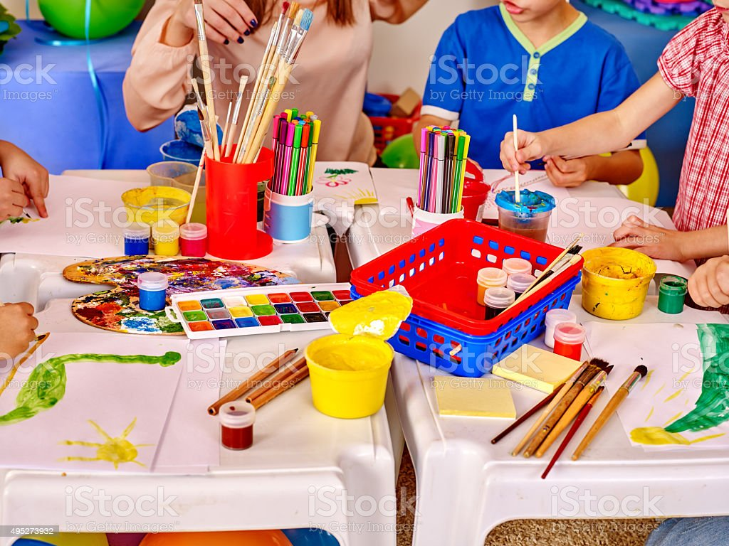 Kids hands holding colored paper and glue on table in stock photo