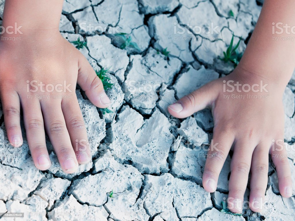 Kids hands on cracked drought soil stock photo