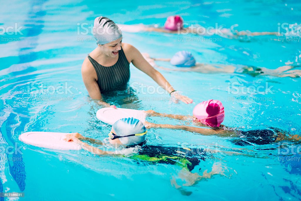 Kids having a race in swimming class stock photo