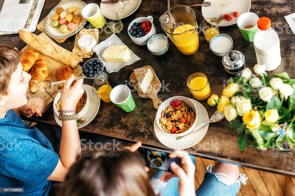 kids having breakfast together at weekend stock photo