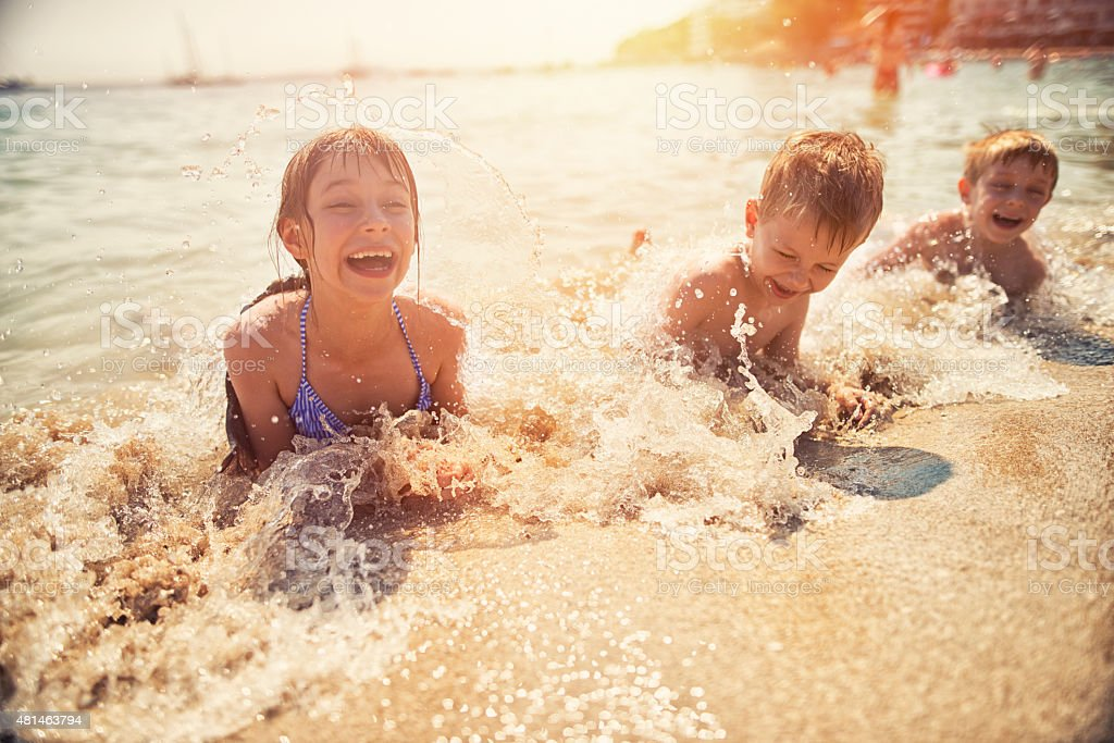 Kids having fun in sea lying on beach stock photo