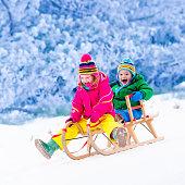 Kids having fun on sleigh ride in snow park