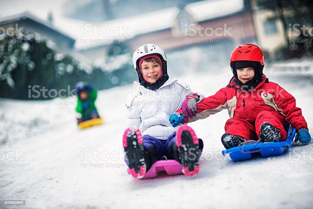 Kids having fun on toboggan race stock photo