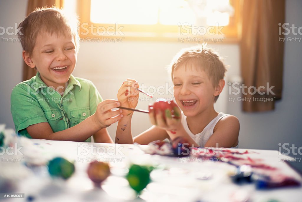Kids having fun painting easter eggs stock photo