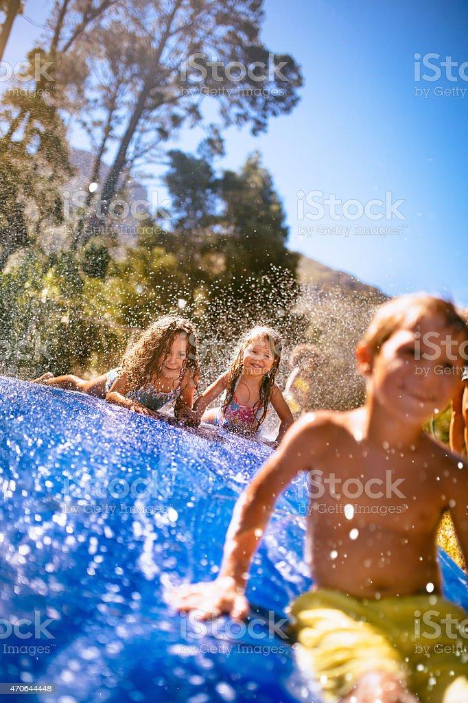 Kids having fun sliding down a slippery water slide stock photo