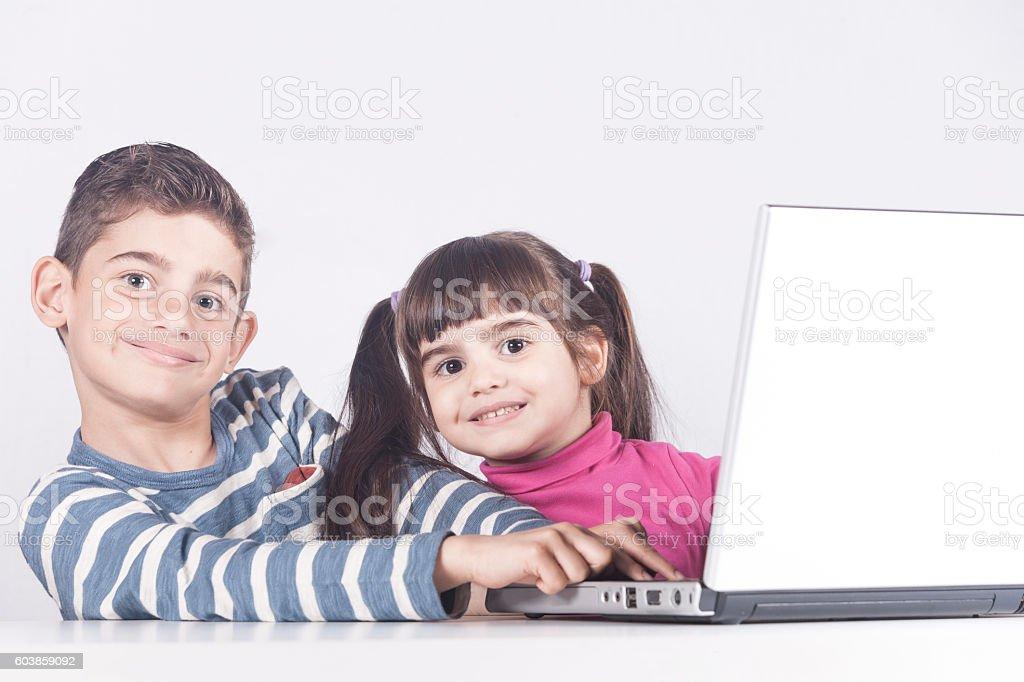 Kids having fun using a laptop computer stock photo