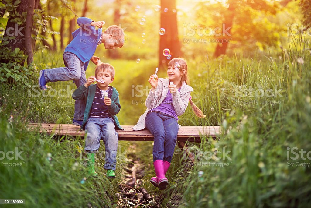 Kids having fun with bubbles stock photo