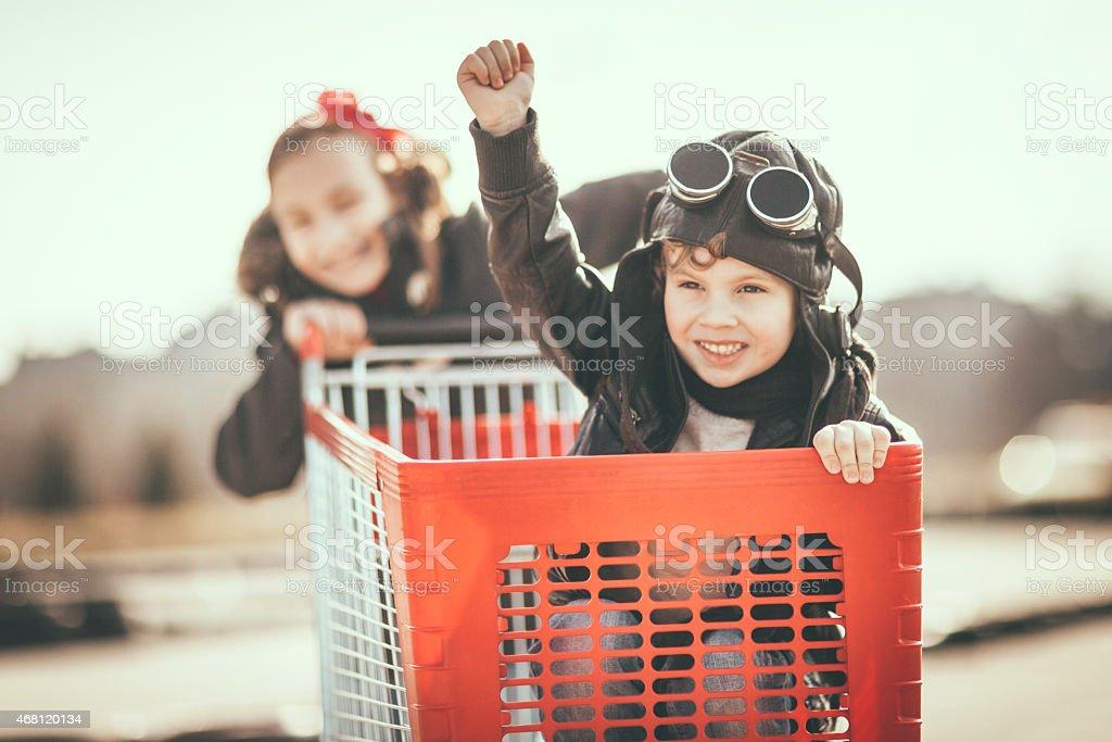Kids having fun with shopping cart stock photo