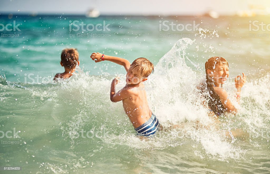 Kids having ultimate fun in sea waves stock photo