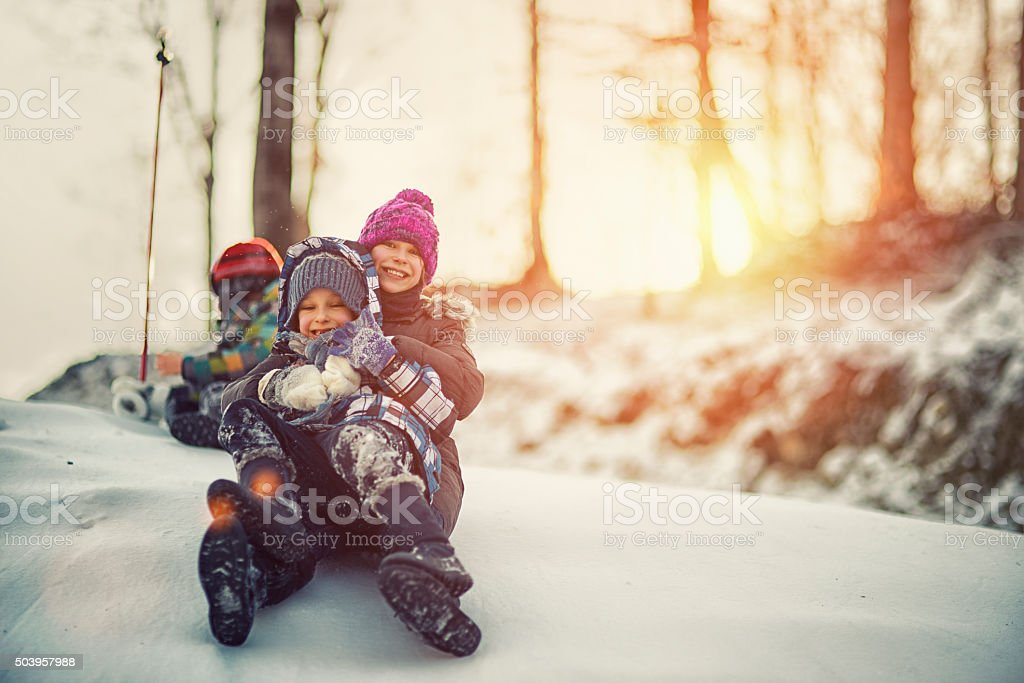 Kids having winter fun sliding on snow stock photo