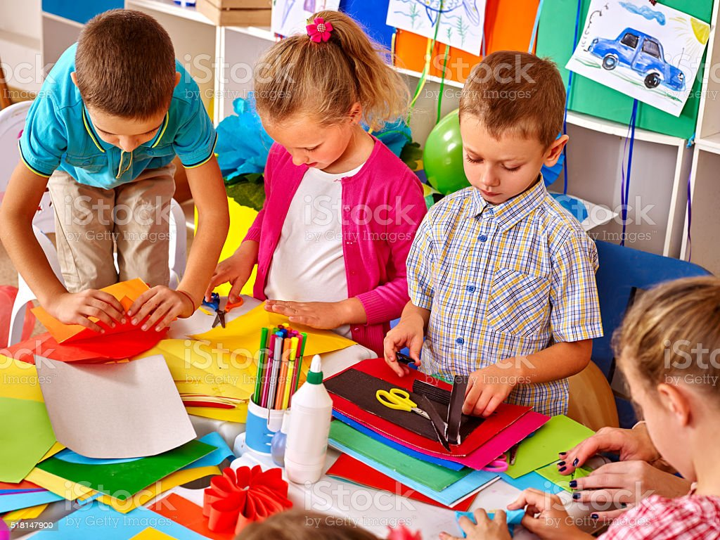 Kids holding colored paper on table in kindergarten stock photo