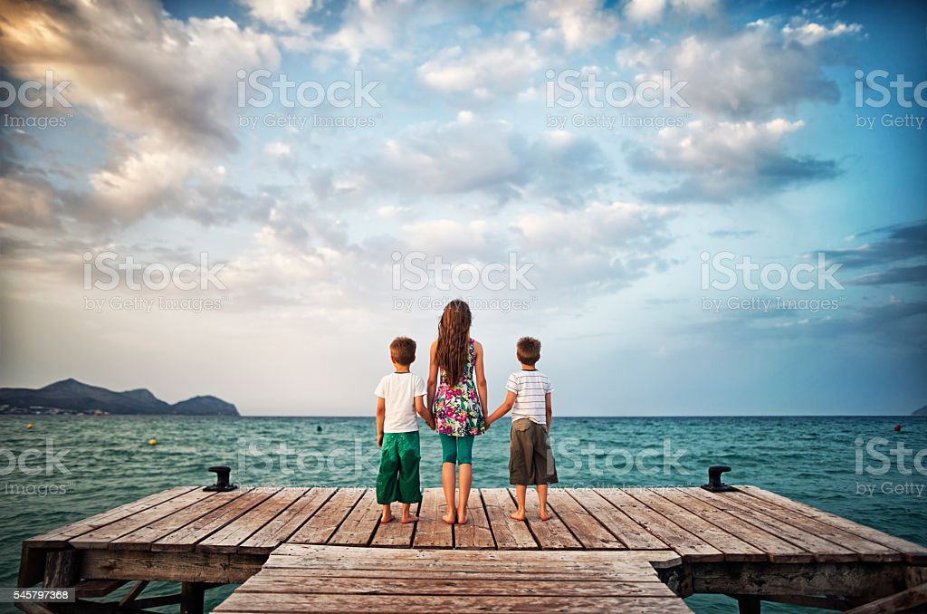 Kids holding hands at sea pier stock photo
