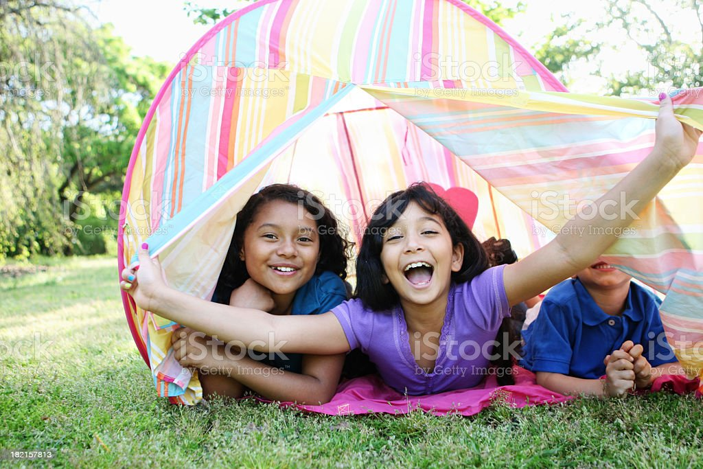 3 kids in a tent opening it and smiling royalty-free stock photo