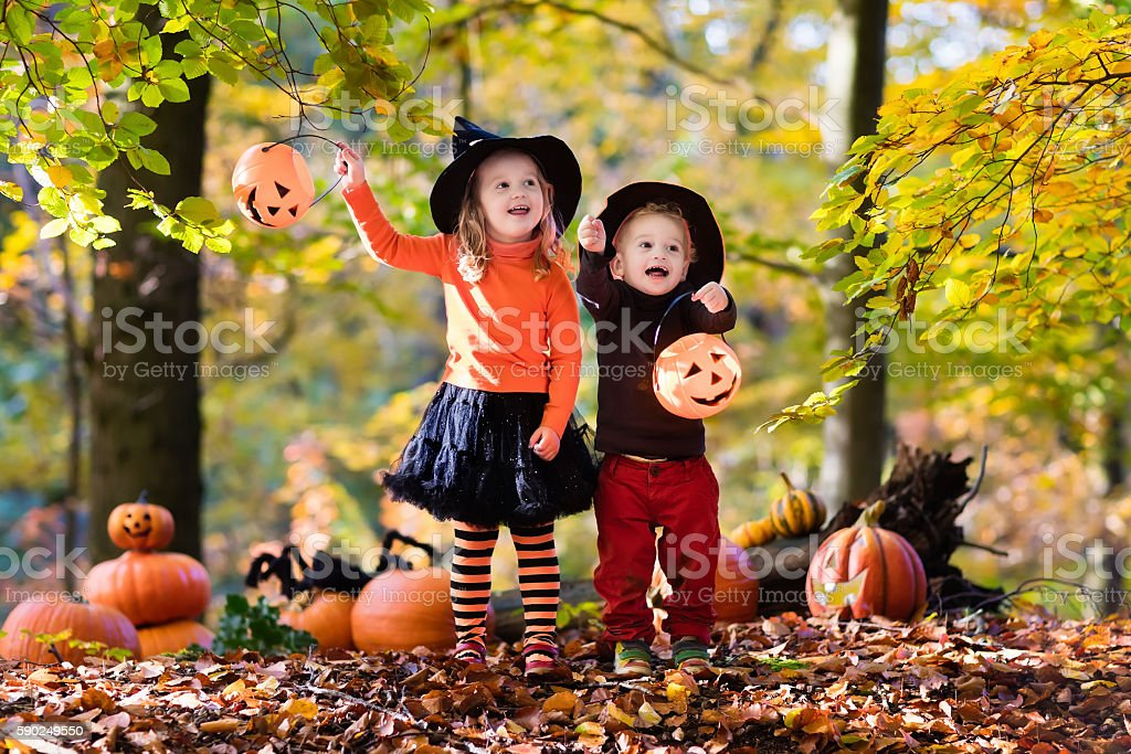 Kids in black and orange hats with pumpkins on Halloween stock photo