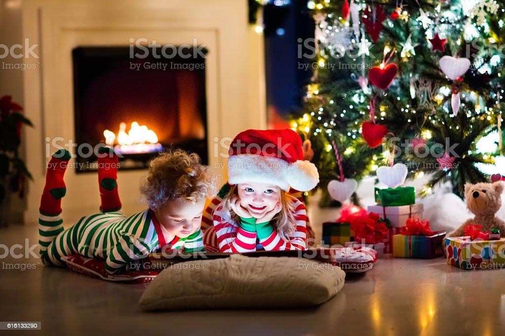Kids in pajamas reading book under Christmas tree stock photo