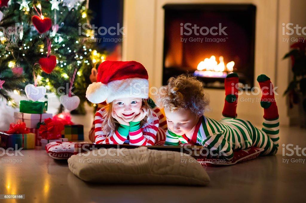 Kids in pajamas under Christmas tree stock photo