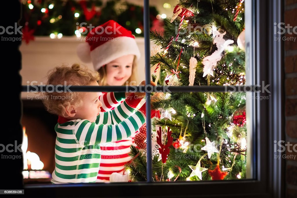 Kids in red and green striped pajamas decorating Christmas tree stock photo