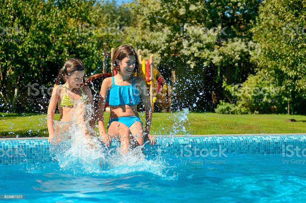 Kids in swimming pool have fun and splash in water stock photo