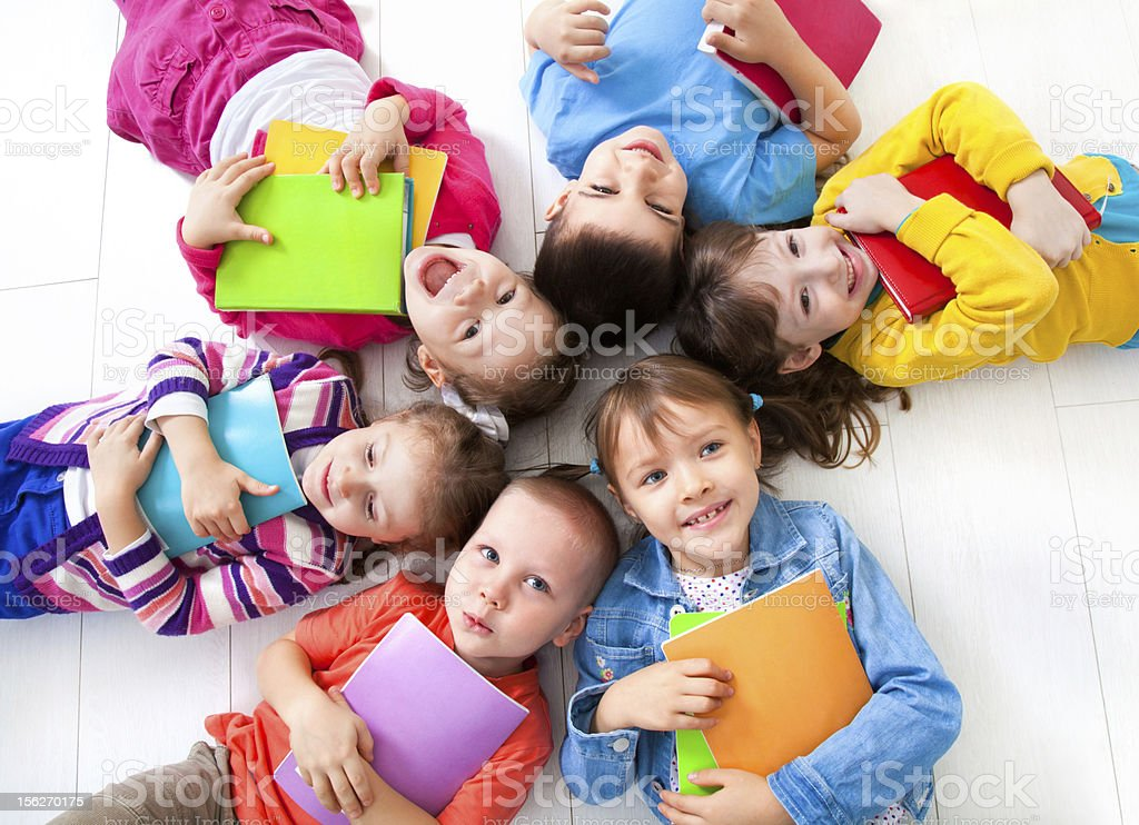 Kids in vibrant colored clothes laying with heads together stock photo