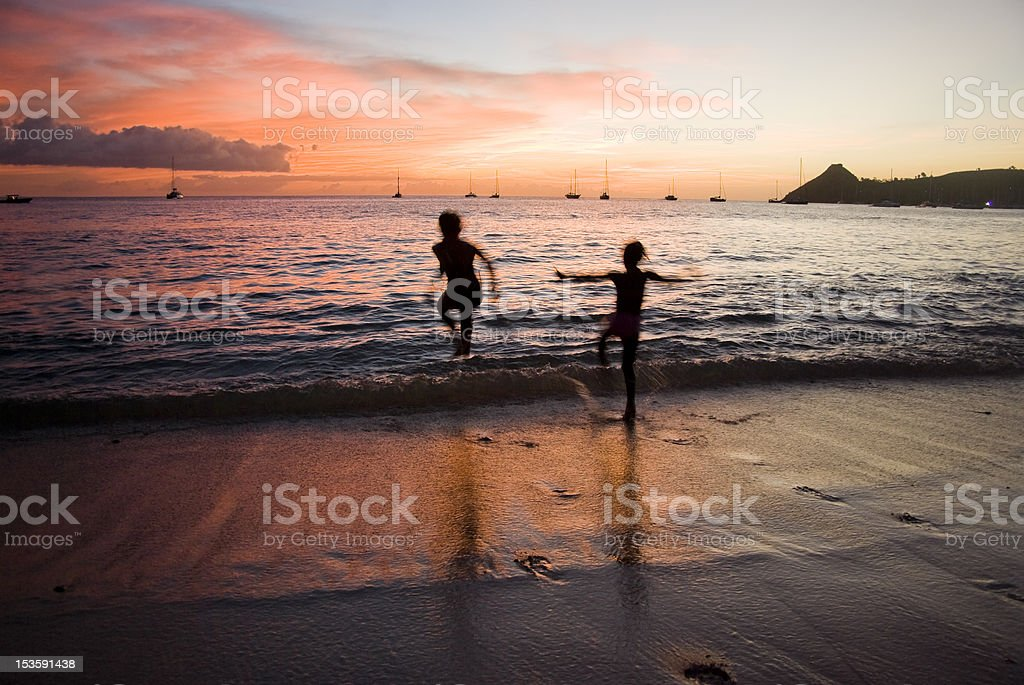 kids jumping in sea at colorful sunset stock photo