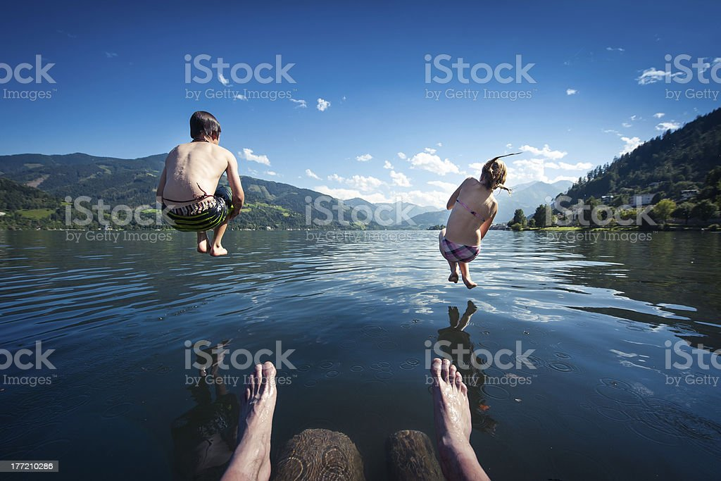 kids jumping into blue lake on summer day stock photo
