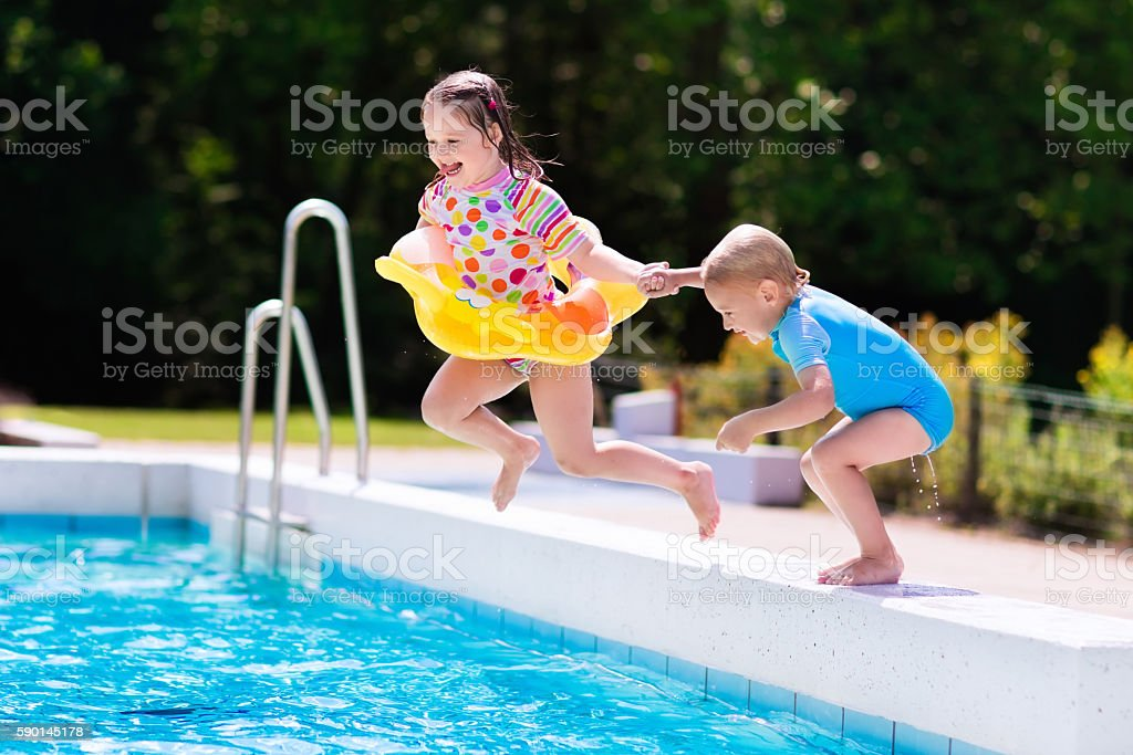 Kids jumping into swimming pool in a tropical resort stock photo