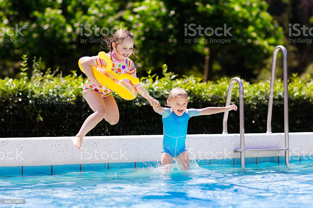 Kids jumping into swimming pool stock photo