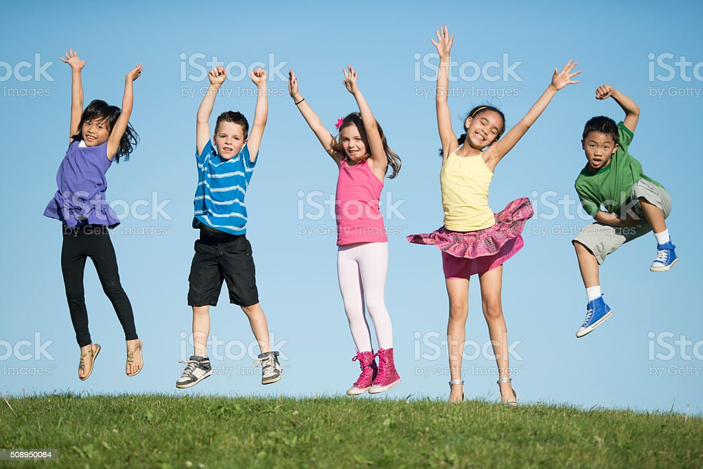 Kids Jumping on a Hilltop stock photo