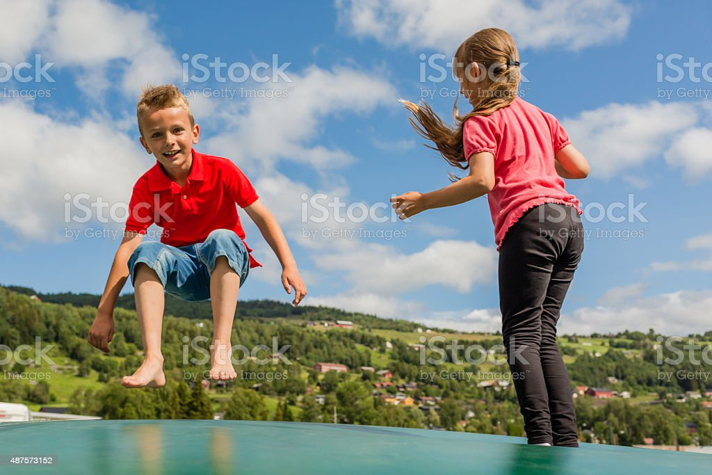Kids jumping on bouncy pillow stock photo