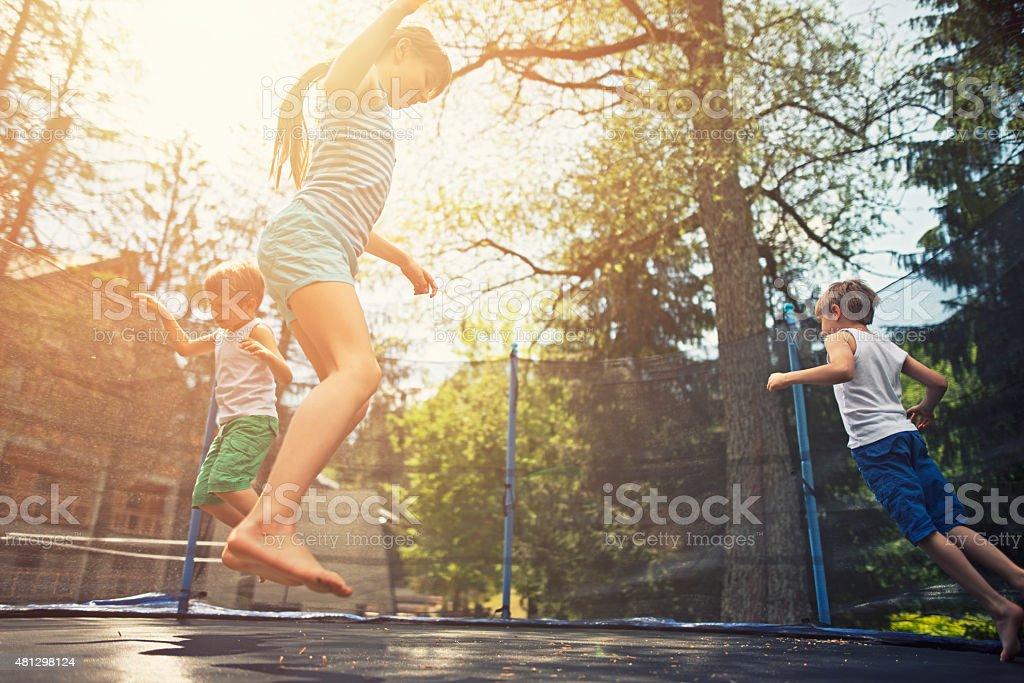 Kids jumping on garden trampoline stock photo