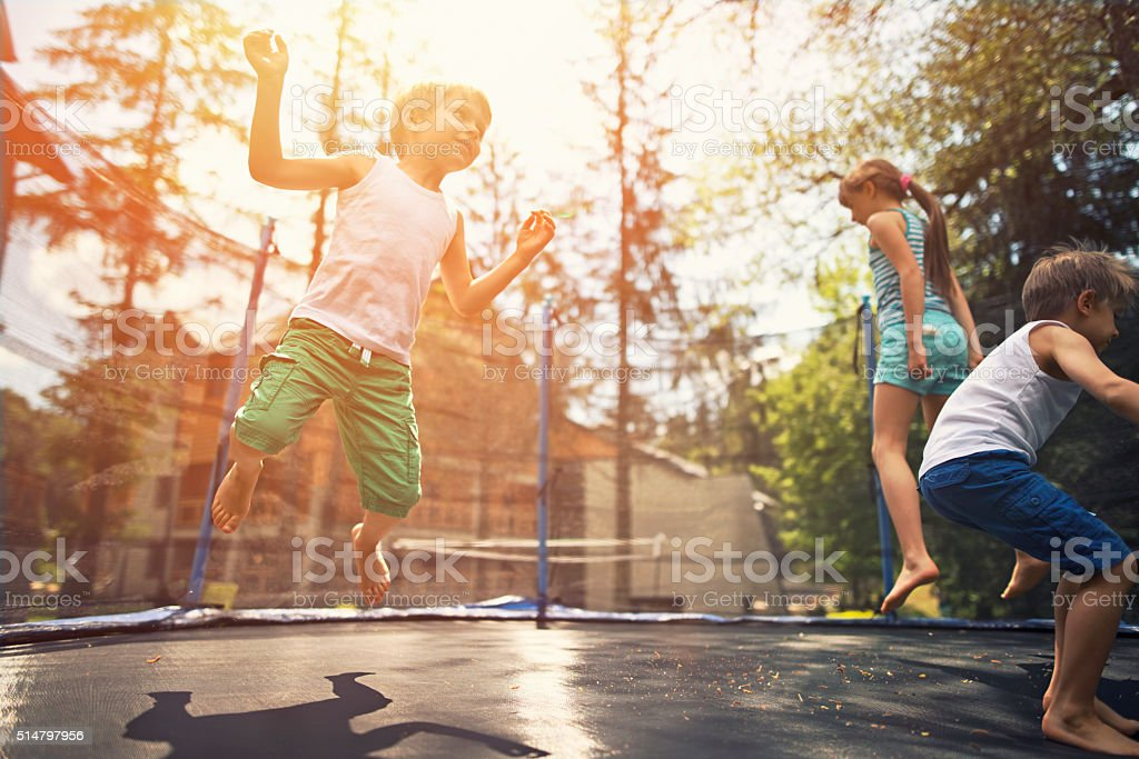 Kids jumping on garden trampoline stock photo