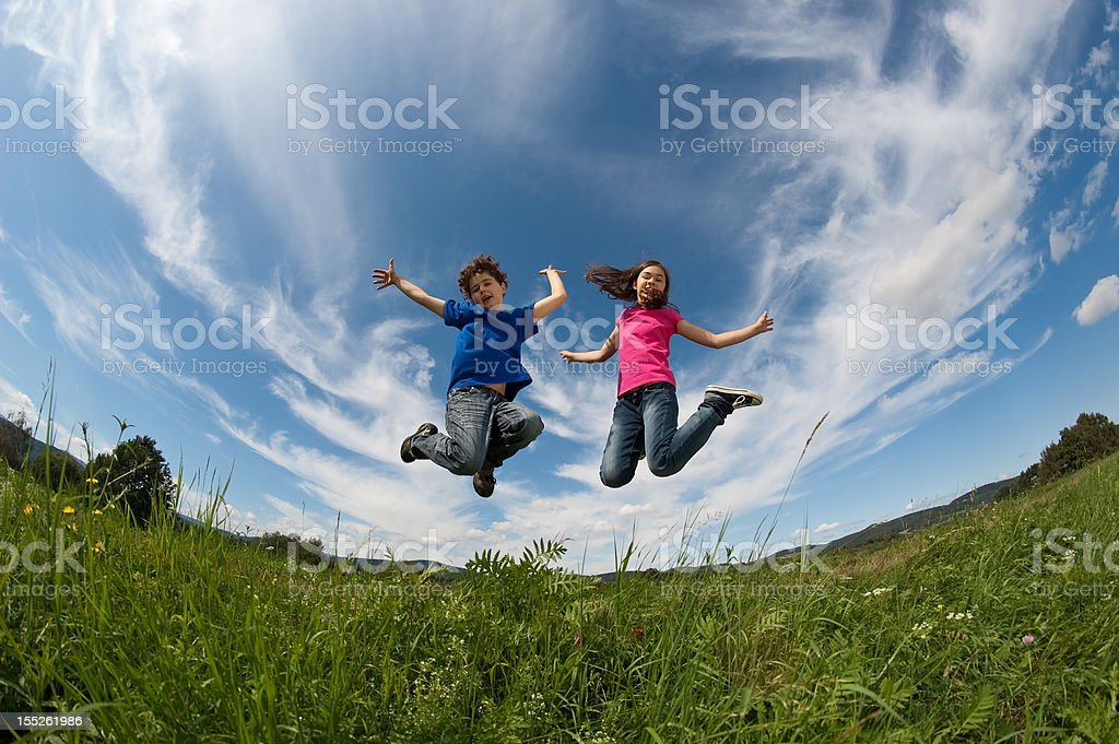 Kids jumping on green meadow royalty-free stock photo