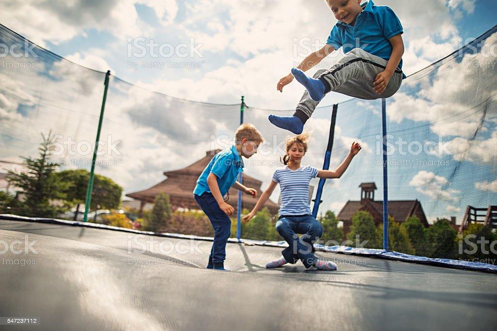 Kids jumping on trampoline stock photo
