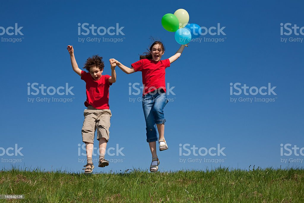 Kids jumping outdoor, holding balloons royalty-free stock photo