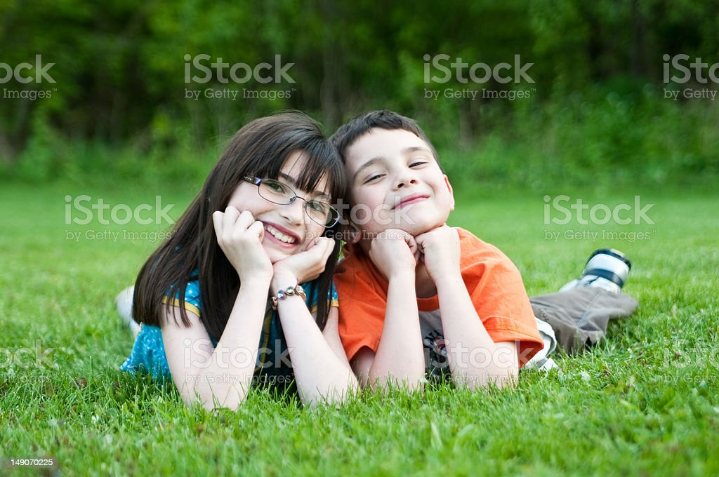 Kids laying in the grass. royalty-free stock photo