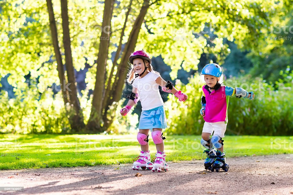 Kids learn to roller skating in summer park stock photo