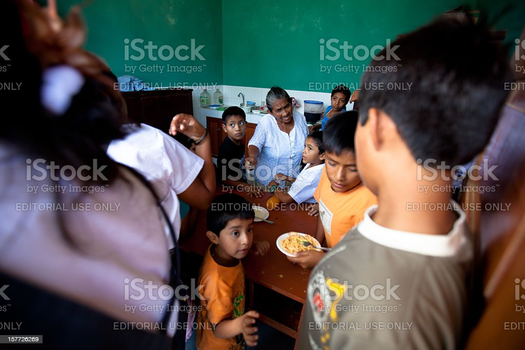 Kids line up to get their lunch in rural Peru royalty-free stock photo