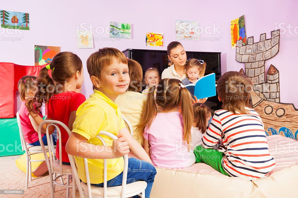 Kids listen to teacher storytelling reading book stock photo