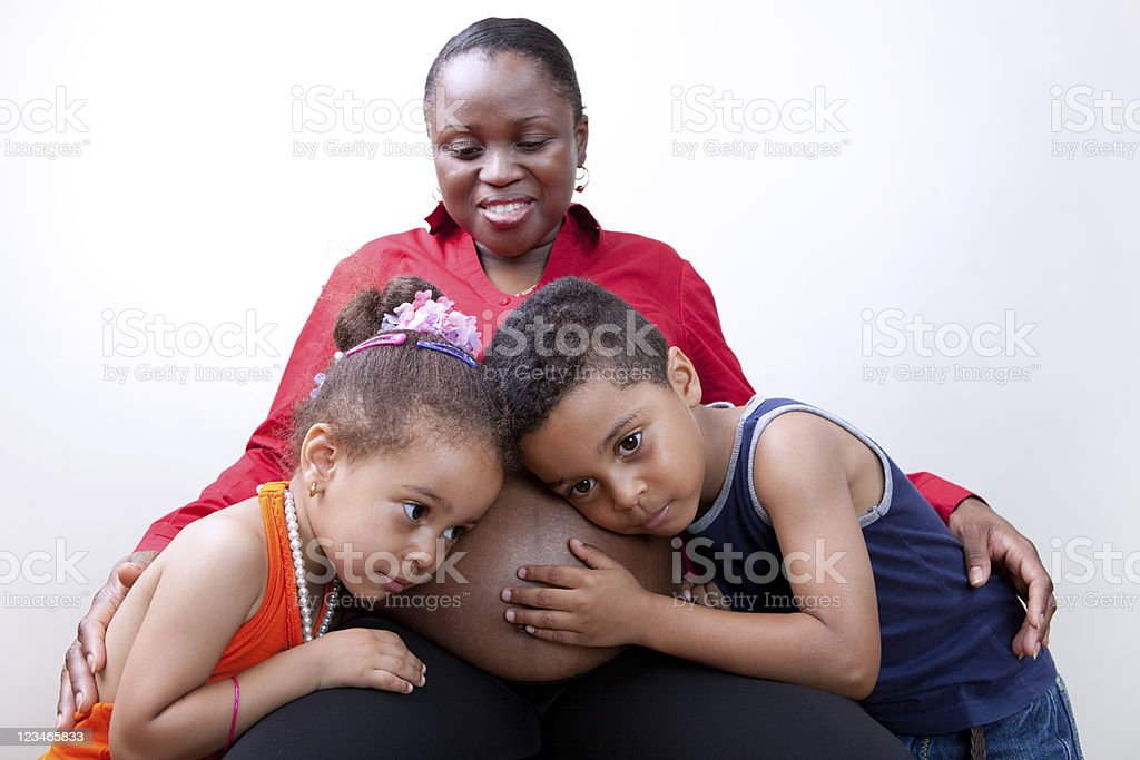 Kids listening to mom`s pregnant belly royalty-free stock photo
