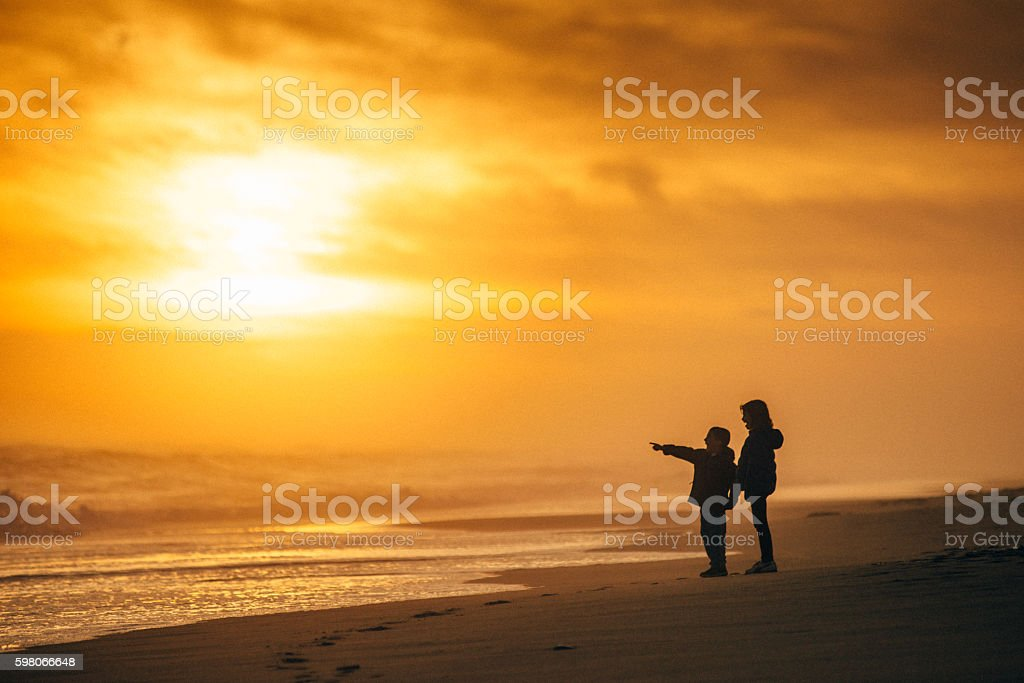 Kids looking at the sea at sunset stock photo