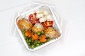 Kids lunch box: peas, carrots, meat balls, tomatoes and cheese