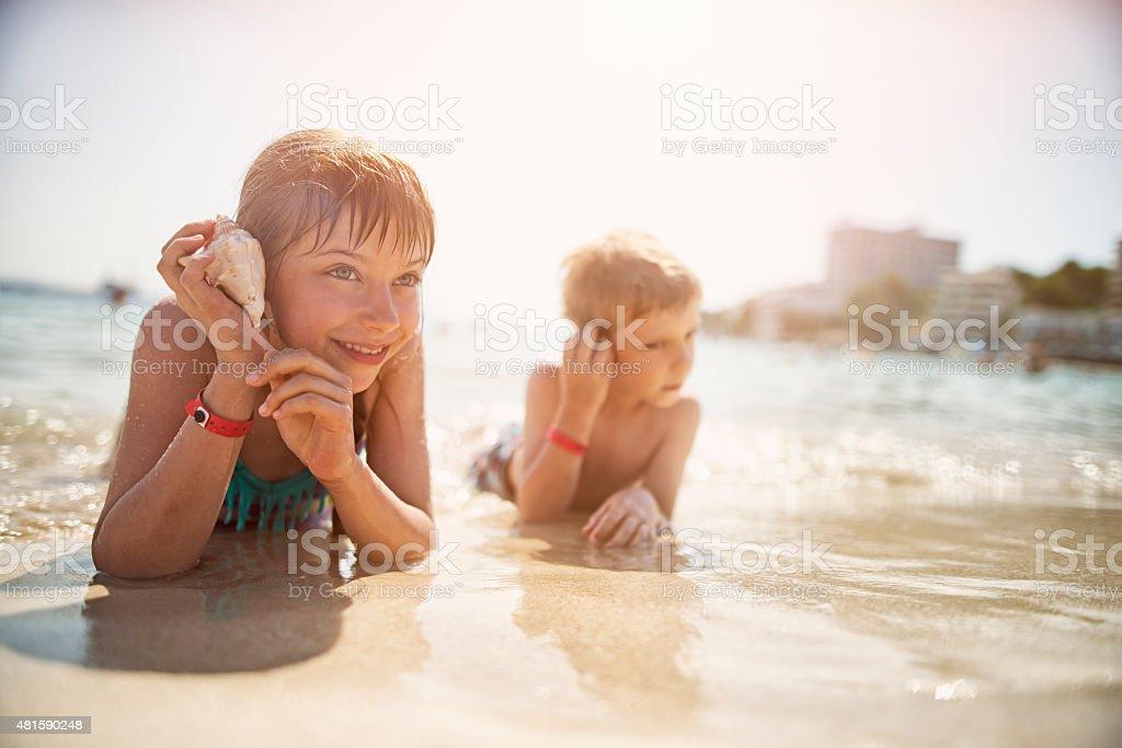 Kids lying on beach listening to sea shells stock photo