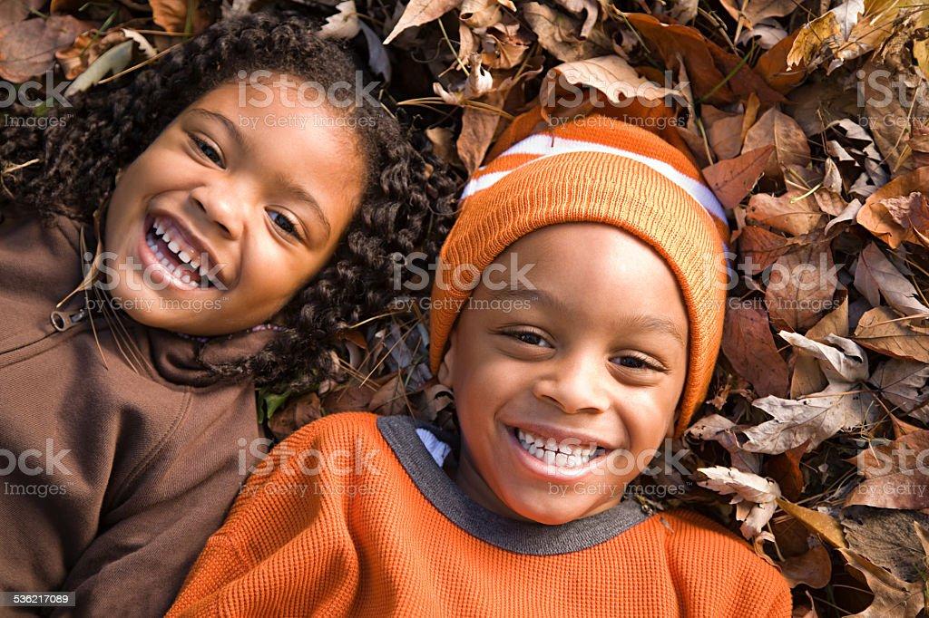 Kids lying on leaves stock photo