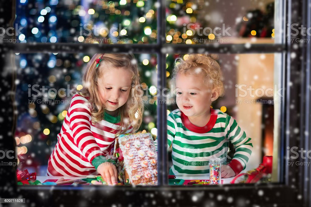 Kids making Christmas ginger bread house in decorated living room stock photo