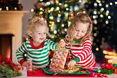 Kids making Christmas ginger bread house in decorated room
